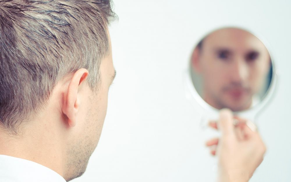 man-looking-at-reflection-in-mirror